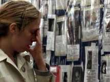 Rachelle Stuckey, 26, cries while looking at the Wall of Prayers at Bellevue Hospital Center in New York, Friday, Sept. 14, 2001. The wall is covered with photos of missing persons from Tuesday's terrorist attack on the World Trade Center. Stuckey did not lose anyone in the attack, but feels sadness for those who did. (AP Photo/CP, Paul Chiasson)